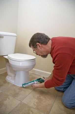 Plumber in Monterey, CA caulks a toilet